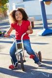 Triciclo del montar a caballo del niño en patio Foto de archivo