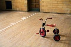 Triciclo en gimnasia vacía Fotografía de archivo libre de regalías