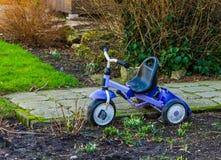 Triciclo estacionado no jardim, brinquedos das crianças, brinquedo popular da criança foto de stock