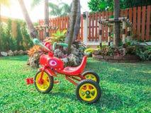 Triciclo rojo de la bici en la hierba verde clara de la llamarada del patio del parque del jardín en casa Imagen de archivo libre de regalías