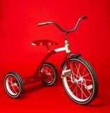 Triciclo rojo del vintage en un fondo rojo brillante Imagen de archivo libre de regalías