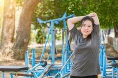 Tricipite grasso delle donne di forma fisica che allunga all'aperto nel parco Fotografia Stock