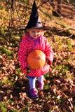 Trick des kleinen Mädchens oder Behandlung im Herbst lizenzfreie stockfotos