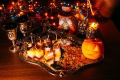 Trick eller fest, halloween tradition: underhållning vid en ferie i form av en canape, slagträn och pumpan head Arkivfoton