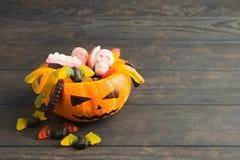 Trick- eller festpumpastålar med färgrika godisar på träbakgrund arkivbild