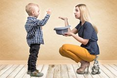 Trick med en kanin En ung moder visar att magiska trick för pysen oavbrutet tjata i hatten Familjvänskapsmatch, underhållning fotografering för bildbyråer