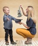 Trick med en kanin En ung moder visar att magiska trick för pysen oavbrutet tjata i hatten Familjvänskapsmatch, underhållning arkivbilder
