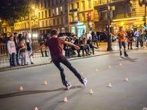 Trick skater negotiates slalom cones on a pedestrian bridge in p Stock Photos