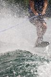 Trick Skier Behind Water Spray. Young man on trick ski going through his routine Stock Photo