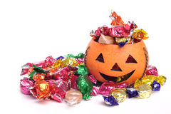Trick Or Treat. Photograph of a pumpkin and candy (sweets) shot in studio against a white background Royalty Free Stock Photography