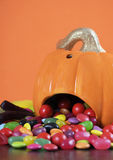 Trick or treat candy spilling out of Halloween pumpkin - vertical closeup. Stock Photography