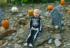 Girl wearing skeleton costume at Halloween decorated outdoors Royalty Free Stock Image