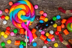 Colorful halloween candies on wood. Trick and treat - colorful halloween candy drops and lollypop on wood close up Stock Image
