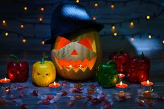 Trick or treat! Favourite autumn holiday. Mystical scary jack-o-lantern in hat and frightening peppers. Sweets, light garland, ca. Ndles are on the background royalty free stock photography