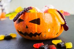 Trick or treat Halloween concept with pumpkin Jack with various candies. On black table royalty free stock photo