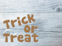 Trick or treat. Halloween greetings written with gingerbread letters on white wood background Royalty Free Stock Images