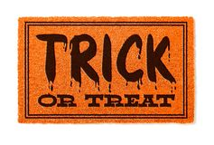 Trick Or Treat Halloween Orange Welcome Mat Isolated on White royalty free stock photo