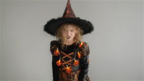 Trick or Treat. Halloween Party. Girl shows the evil sorceress. Child is wearing a black-and-orange dress and hat. From stock video