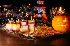 Trick or treat, halloween tradition: entertainment by a holiday in the form of a canape, bats and the pumpkin head Stock Image