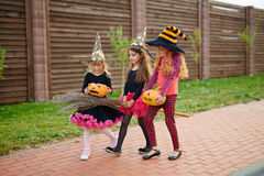 Trick-or-treat promenade. Little halloween witches in hats moving down pavement during trick-or-treat promenade Stock Photo