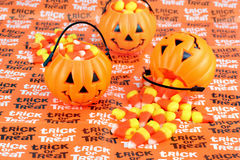 Trick or Treat Pumpkins with Candy. Three pumpkins filled with candy corn on a Trick or Treat tablecloth Royalty Free Stock Photos