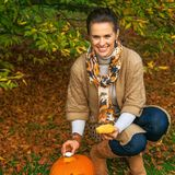 Smiling woman putting candle in carved Halloween pumpkin Stock Photography