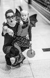 Mother and child on Halloween at mall pointing at something. Trick or Treat. surprised trendy mother and child in bat costumes on Halloween at the mall pointing Royalty Free Stock Image