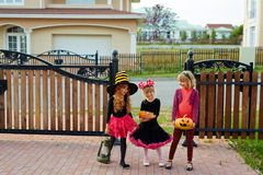 Trick-or-treat team. Trick-or-treat girls standing by fence of house they visited Royalty Free Stock Images