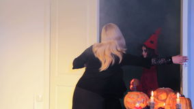 After Trick-Or-Treat. Woman ways good-bye to children in costumes who sang a trick-or-treat song and closes the door stock video footage
