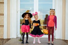 Trick-or-treaters by door. Happy youthful girls with halloween treats standing by door of house Stock Photos