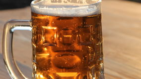 A trickle of bubbles rising in the beer. A mug of cold light beer stock footage