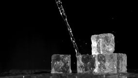 Trickle of water in super slow motion flowing on ice cubes. Against a black background stock video