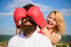 Tricks every woman needs to know. Girl smiling face covers male face with boxing gloves. Cunning tricks to win. Guess. Tricks every women needs to know. Girl stock image