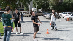 Tricks with football on the head. NOVOSIBIRSK, RUSSIA - AUGUST 14, 2015: Young man performing tricks with a football on the head during street sport event in the stock footage