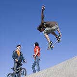 Tricks at skatepark. Kids hang out and do tricks at the skatepark Stock Image