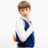 Tricky boy. Portrait of a dark-haired boy on a gray background. He cheats Royalty Free Stock Photography