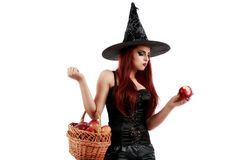 Tricky witch offering a poisoned apple, Halloween theme Royalty Free Stock Photo