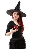 Tricky witch offering a poisoned apple, Halloween theme Stock Image