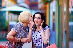 Tricky young women gossip on the street. Tricky young women gossip on the city street stock image