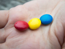 Tricolor bonbons in a hand Royalty Free Stock Image