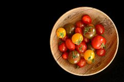 Tricolor cherry tomatoes on black royalty free stock photography