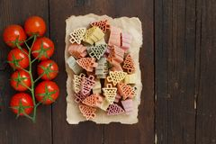 Tricolor fir tree shaped pasta and tomatoes. Tricolor fir tree shaped pasta and cherry tomatoes on wood Stock Images