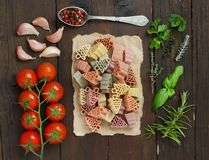 Tricolor fir tree shaped pasta, vegetables and herbs. On wood Stock Image