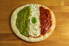 Tricolor pizza. A Three colour pizza with mozzarella, basil, tomato and pesto Stock Photography