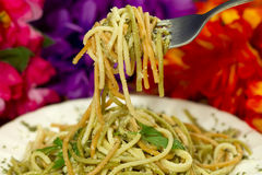 Tricolor Spaghetti On Fork. Spaghetti made of tomato, spinach and regular flower flavors with parsley and parmesan cheese shot close up on a fork with studio Royalty Free Stock Photography