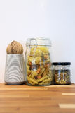 Tricolor spiral pasta and grain in glass jar on wooden table Royalty Free Stock Image