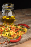 Tricolor spiral pasta with spices on a dark wooden table. Royalty Free Stock Image
