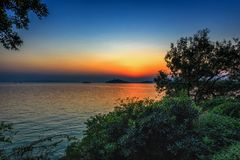 Tricolor Sunset. An autumnal sunset at the Tai Lake with an island in the background royalty free stock photos