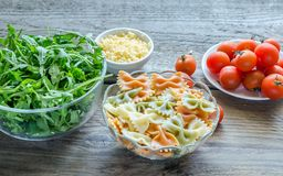 Tricolore farfalle with arugula, parmesan and cherry tomatoes Royalty Free Stock Image