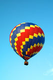 Tricolored hot air balloon flying in sky Royalty Free Stock Photo